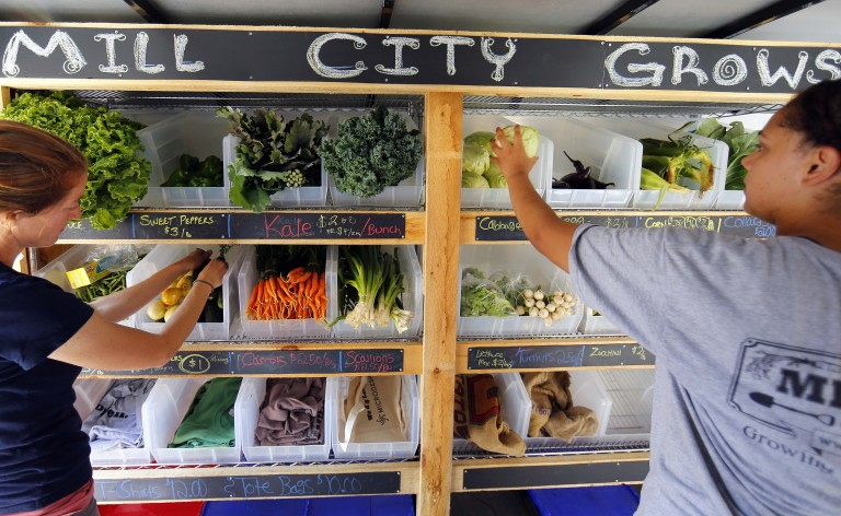 Lydia Sisson, left, founding co-director of Mill City Grows and Tasha Abraham stock the mobile market with produce in Lowell, Mass. Wednesday, July 29, 2015. (Winslow Townson for The Boston Globe)